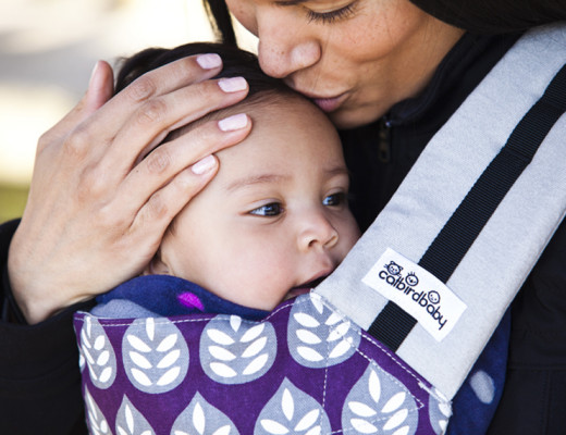 Mom kisses baby's head while carrying her in the pikkolo buckle carrier.